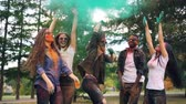 sale : Slow motion of multiethnic group of friends students jumping and throwing paint powder then dancing and laughing in bright clouds. Nature, party and fun concept. Vidéos Libres De Droits
