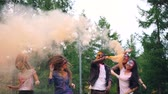 eğlenceli : Slow motion of girls and guys dancing and jumping with smoke flares at outdoor party, skin and clothes are covered with bright paint. Emotions and holidays concept.