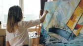 acrílico : Good-looking girl artist is busy painting seascape on canvas using color palette, brush and canvas on easel working in nice studio. Talented people and work concept. Vídeos