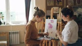 şövale : Female student of art school is painting flowers with oil paints while her teacher good-looking young woman is giving her advice pointing at picture.