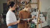 learner : Young lady student is painting on canvas using oil paints while her teacher experienced artist is standing near her and looking at picture. Pictorial art and people concept. Stock Footage