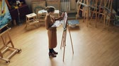 quadro : High angle view of young woman painter working in studio standing in front of easel and painting holding brush and palette. Wooden furniture, artworks and tools are visible.