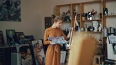 オイル : Creative young lady is painting with oil paints working in studio alone standing in front of easel with beautiful artworks in background. Hobby and work concept.