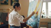 peinture à l huile : Professional artist young woman is painting seascape with acrylic paints finishing marine landscape ship and sea waves working alone in cozy studio. People and work concept. Vidéos Libres De Droits