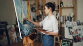 peinture à l huile : Cheerful young woman artist is painting beautiful picture marine landscape using oil paints then looking at masterpiece and smiling enjoying her work. Vidéos Libres De Droits