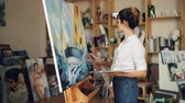 eğlenceli : Good-looking young woman in casual clothing is painting in workroom then looking at picture, evaluating her work and smiling enjoying beautiful image. Stok Video