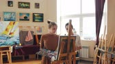 obrazy olejne : Female art teacher is working with good-looking young girl student painting picture giving advice standing in front of easel with paintbrush and palette. Wideo