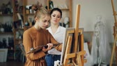 peinture à l huile : Experienced art teacher is working with pretty girl talanted student painting picture and talking sharing experience indoors in workroom full of artworks.