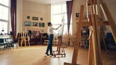 peinture à l huile : Young female painter is painting picture indoors working inside light workshop alone. Wooder easels, authentic artworks and arts tools are visible.