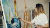 peinture à l huile : Blond girl painter is working in studio depicting sea landscape and boat on canvas using brush and tempera paints looking at picture and enjoying her occupation. Vidéos Libres De Droits