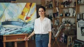 peinture à l huile : Portrait of pretty young lady painter looking at camera and smiling standing near her beautiful picture on easel in modern studio enjoying her work.