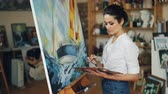 mestre : Female artist is concentrated on work painting beautiful picture sea and boat with oil paints working alone in studio using bright colors. Artistry and creativity concept. Vídeos