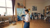 peinture à l huile : Serious artist is working in workroom standing in front of easel with palette and brush and painting picture boat and sea waves in acrylic paints. People and hobby concept.