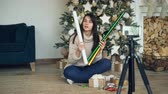 papel de embrulho : Creative young lady is recording video for online vlog about gift-wrapping for Christmas holidays. Girl is showing wrapping paper, boxes, ribbons and scissors.