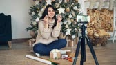 presente de natal : Cheerful woman vlogger is recording tutorial about gift wrapping sitting near Christmas tree and holding bright packing paper, ribbons, boxes and scissors.