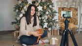 блогов : Skillful woman blogger is teaching her followers to decorate Christmas gifts sitting on floor holding present box and ribbon and recording video with smartphone.