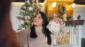 presente de natal : Point of view shot of good-looking brunette taking selfie on Christmas day holding camera and posing with hand gestures and gift box expressing positive emotions.