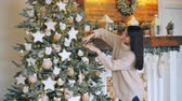 perfection : Smiling young lady is decorating Christmas tree with balls, stars and lights touching decorations and enjoying festive activity. Holiday and traditions concept.