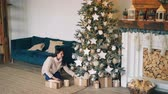 nowe mieszkanie : Good-looking girl in warm sweater is bringing gift boxes to Christmas tree, putting them under fir-tree and smiling then touching decorations. Holidays and presents concept.