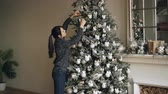 perfection : Smiling young woman is decorating green Christmas tree with beautiful balls creating authentic design getting ready for winter holidays. People and interior concept.