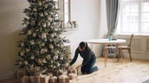 abend : Attractive girl is bringing gift boxes to Christmas tree, putting them under fir-tree and smiling then touching beautiful decorations. Holidays and presents concept. Stock Footage