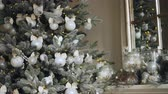 nowe mieszkanie : Close-up shot of awesome artificial New Year tree with beautiful silver balls hanging on its branches and lights glittering on fir-tree. Decorated mantel is visible.