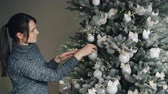 ocasião : Joyful young woman is decorating New Year tree with stylish silver balls and golden lights enjoying festive activity in December. People and traditions concept.