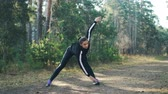 samotność : Attractive young sportswoman is doing sports in park on sunny autumn day wearing modern black tracksuit. Slim girl is bending forward and moving arms.