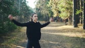 zoom out : Zoom out of slender brunette in black sportswear doing exercises outdoors in park among green and yellow trees on sunny autumn day. Youth and wellness concept. Stock Footage