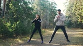 witalność : Cheerful students are doing sports together in park squatting and smiling enjoying exercises and nature. Man and woman are wearing modern tracksuits. Wideo