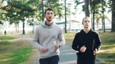 konsantre : Bearded young man is jogging with his female friend in park exercising outdoors wearing modern sportswear concentrated on running. Healthcare and people concept.