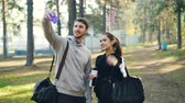pulgar arriba : Happy friends sportive young people are taking selfie using smartphone after outdoor practice in park. Man and woman are holding bags and posing for camera.