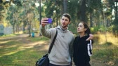 wi fi : Attractive woman and man are making online video call with smartphone in park after sports training. Guy is holding device, people are waving hands, talking and laughing.