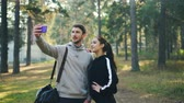 contato : Sportive girlfriend and boyfriend are making online video call using smartphone standing in park together looking at device showing thumbs-up, waving hand and laughing.
