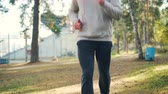 Tilt-up shot of handsome guy in trainers and tracksuit jogging in park wearing headphones and enjoying physical activity and autumn nature. People and sports concept. Archivo de Video