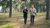 sportovkyně : Dolly shot of attractive girl and guy jogging in park together focused on practice. Woman is wearing sweatshirt and leggings, man is wearing tracksuit. Dostupné videozáznamy
