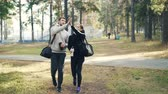 sportovkyně : Dolly shot of happy girl and guy walking together in city park wearing sportswear and holding water bottles and bags. People are talking, laughing and doing high-five. Dostupné videozáznamy