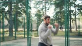 físico : Bearded guy is training in park making boxing movements exercising alone in recreational area on warm autumn day. Sports, fighting and sportsmen concept.