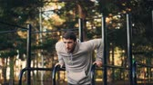 párhuzamos : Strong young man is doing triceps dips on parallel bars in city park exercising outdoors in the morning in summer. Active lifestyle, workout and nature concept.