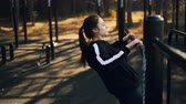 físico : Fit young woman is exercising outdoors doing pull-ups on low horizontal bar in park in autumn morning training alone. Active lifestyle and sports concept. Stock Footage