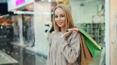 Portrait of pretty long-haired blonde in trendy clothing looking at camera and smiling standing alone in shopping mall holding paper bags. People and shops concept.