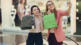 Happy shopaholics are taking selfie with paper bags in shopping mall using smartphone camera holding device and posing, laughing and having fun. Youth lifestyle concept. Vídeos