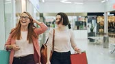 Attractive young women are walking in shopping center with bags, looking around, talking and laughing having fun enjoying new collection of clothing.