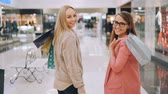 Slow motion of happy young women friends walking together in shopping mall holding bright bags then turning to camera and smiling. Shopaholics and shops concept.