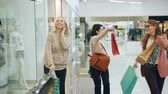 sbírka : Group of happy girls is having fun in shopping center walking with paper bags, laughing and dancing pointing at goods in shop windows. Youth and shopaholics concept.