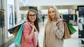 Portrait of attractive young ladies with paper bags standing in shopping mall holding purchases and looking at camera with happy smile. Customers and shops concept. Vídeos