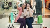 Pretty young women are taking selfie using smartphone camera sitting on bench in shopping mall and having fun. Modern technology, shops and friends concept. Vídeos