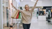 Pretty blonde is having fun in shopping mall listening to music through headphones, dancing with paper bags and looking around at new trendy clothing.