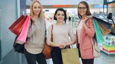 Portrait of good-looking girls wearing trendy clothing and accessories holding shopping bags in large shopping mall looking at camera and smiling. People and stores concept.