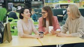 tea time : Good-looking girls are toasting and clinking glasses with drinks sitting in cafe in shopping mall then chatting and laughing having fun together. Friendship and leisure concept.